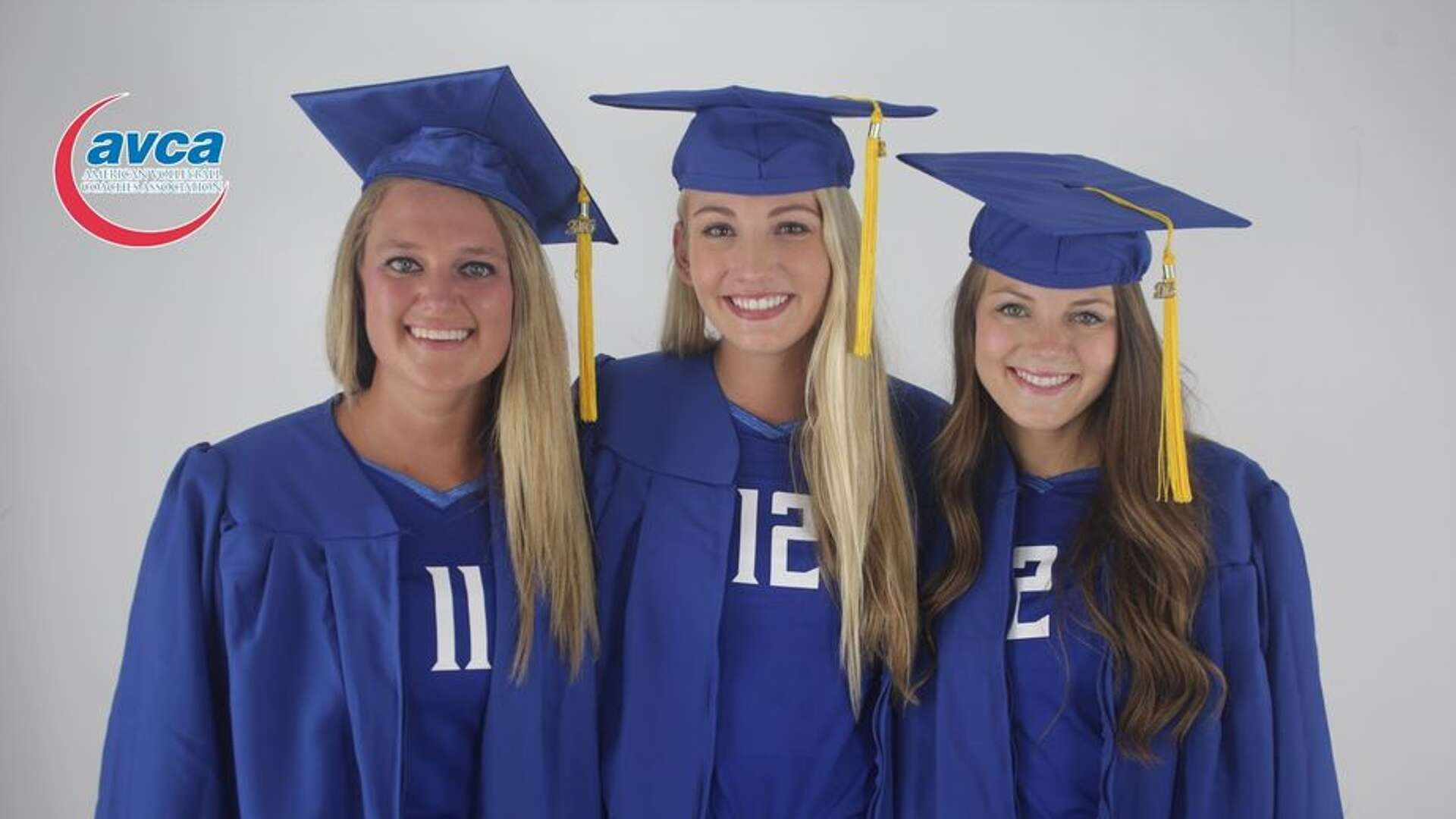 Volleyball players pose in graduation regalia.