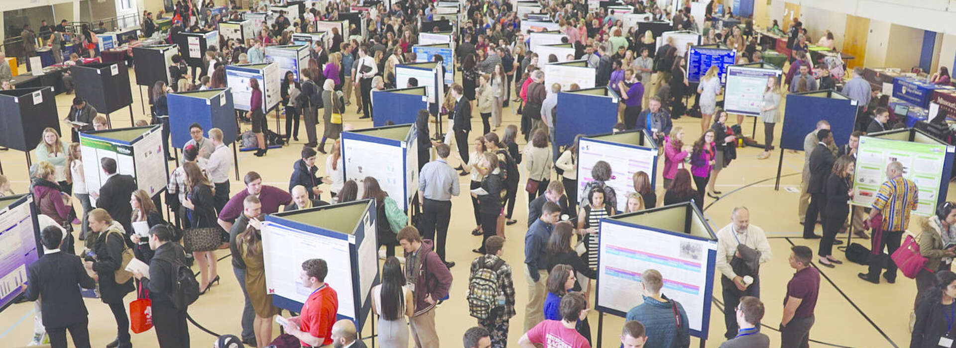 Hundreds of people reviewing large posters of research from above