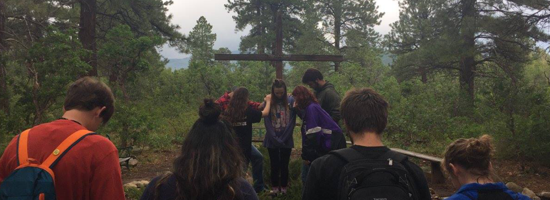 Students in the mountains praying around a cross