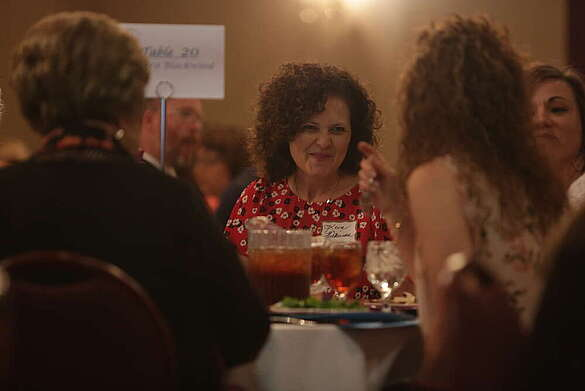 Woman talking with others around a table eating