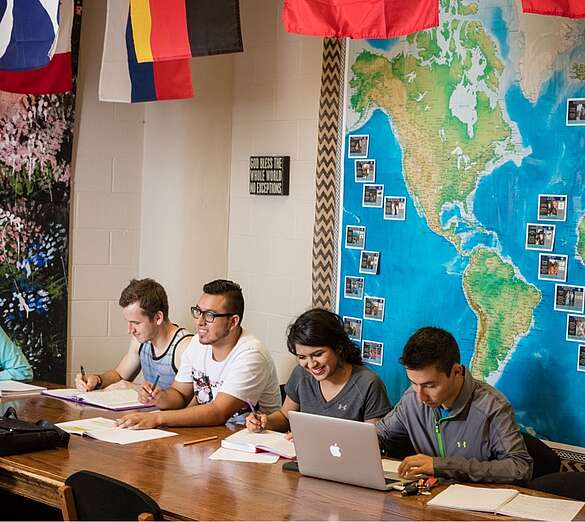 4 Students in a missions class with world flags and map of the world