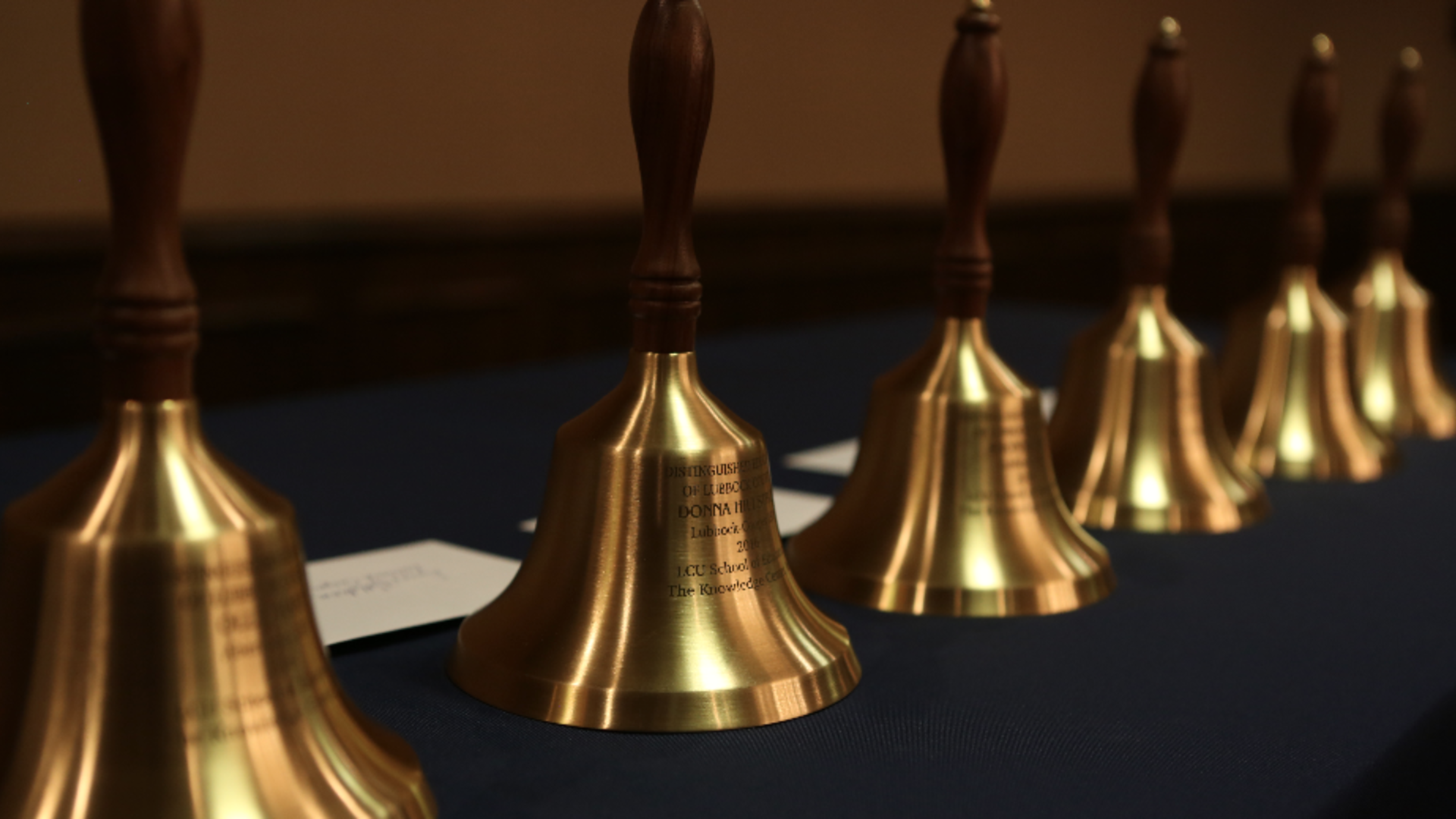 line of inscribed golden bells on table
