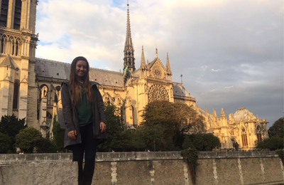 Audrey Bradley standing in front of the Notre Dame Cathedral, Paris, France