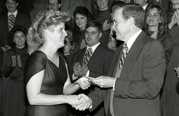 Historical photo of Dr. Wayne Hinds presenting an award to a choir member